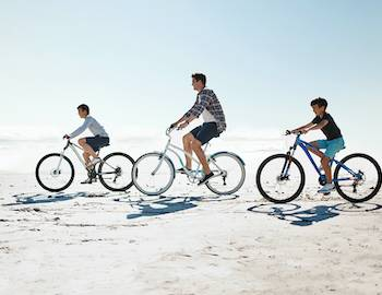 family biking on beach