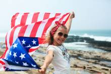 A young girl on the beach with an American flag